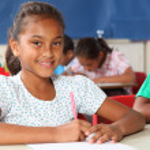 Schoolgirl in classroom writing — Stock Photo