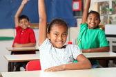 School children arms raised in class — Stock Photo