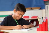 Young school boy 10 writing at his classroom desk — Stock Photo