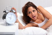 Woman overslept with alarm clock — Stock Photo