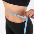 Slim woman with a tape measure around her waist — Stock Photo