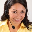 Pretty female receptionist using headset telephone — Stock Photo