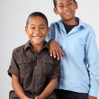 Two school boys pose happily together in studio — Stock Photo