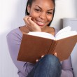 Beautiful happy african girl reading a book — Stock Photo