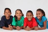 Smiling school kids on floor — Stock Photo