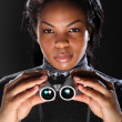 Female secret agent spy holding binoculars - Stock Photo