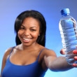 Girl holding out sharply focused bottled water — Stock Photo