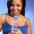 Beautiful smiling black woman with bottled water — Stock Photo