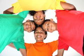 Four school mates in a huddle — Stock Photo