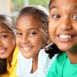 Row of three smiling young school girls sitting in class - Stock Photo