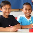 Two happy school boys sitting to their desk in class — Stock Photo