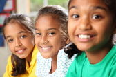 Row of three smiling young school girls sitting in class — Stock Photo