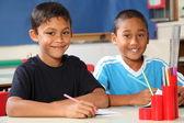 Due ragazzi scuola felice seduti alla loro scrivania in classe — Foto Stock