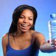 Beautiful girl laughing and holding bottled water — Stock Photo