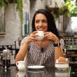 Girl drinking coffee in cafe — Stok fotoğraf
