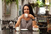 Girl drinking coffee in cafe — Stock Photo