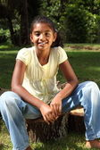 Young girl sitting on log — Foto de Stock