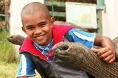 Smiling boy with giant tortoise — Stock Photo