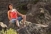 Joven sentada en piedra — Foto de Stock