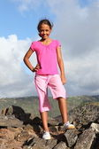 Young girl standing on the mountain summit — Stock Photo