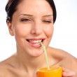 Beautiful young woman drinking juice from orange — Stock Photo