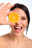 Excited beautiful young woman with orange fruit — Stock Photo
