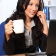Beautiful business woman has coffee at work — Stock Photo