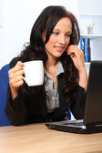 Beautiful business woman has coffee at work — Stockfoto