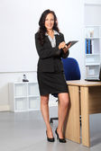 Beautiful business woman standing with clipboard — Stock Photo