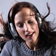 Beautiful woman listening to music on headphones — Stock Photo #6121570