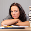 Tired from homework woman rests chin on desk — Stock Photo