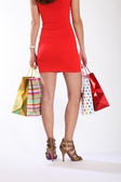 Sexy legs of woman standing with gift bags — Stock Photo
