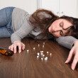 Young woman overdose on pills lying on floor — Stock Photo