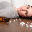 Wide eyed woman lying on floor with pills — Stock Photo
