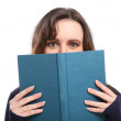 Woman looks up from reading a hard cover book — Stock Photo #6132257