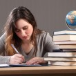 Young student girl writing with books around her — Stock Photo