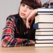 Tired student girl resting on stack of books — Stock Photo