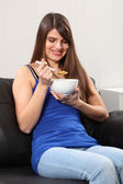 Cheerful woman at home eating breakfast cereal — Stock Photo