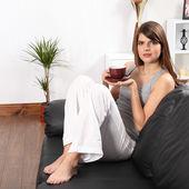 Beautiful woman at home on sofa drinking coffee — Stock Photo