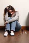 Teenage girl depressed sitting with pills on floor — Stockfoto