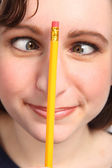 Funny cross eyes of woman with pencil on her nose — Stock Photo