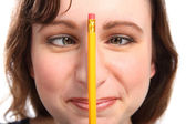 Fun moment as girl holds pencil between her eyes — Stock Photo