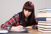 Young student girl doing homework writing in book — Stock Photo