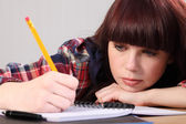 Busy student girl writing homework with pencil — Stock Photo
