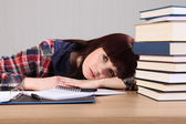 Young student tired from homework head on desk — Stock Photo