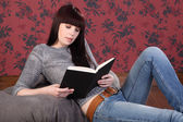 Beautiful girl at home on bean bag reading a book — Stock Photo