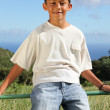 Smiling boy sitting on fence — Stock Photo