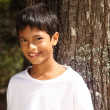 Close up young boy big smile leaning against tree — Stock Photo