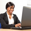 Happy black woman using laptop at office desk — Stock Photo