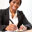 Happy black business woman signing document — Stock Photo #6165381